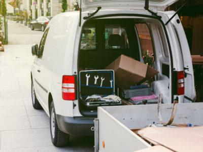 En vit skåpbil med öppen balklucka, full med verktyg