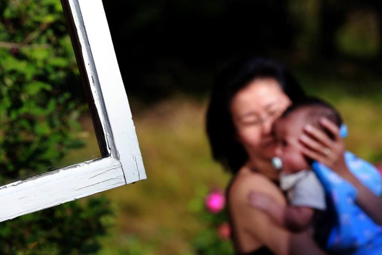 EN person håller i ett barn utanför ett fönster på sommaren