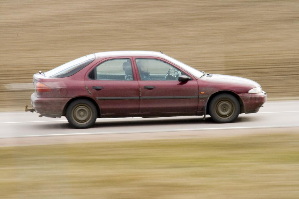 En röd bil åker på en landsväg