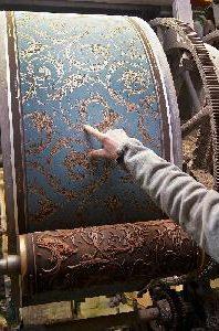 En hand som pekar på en mönstrad tapet