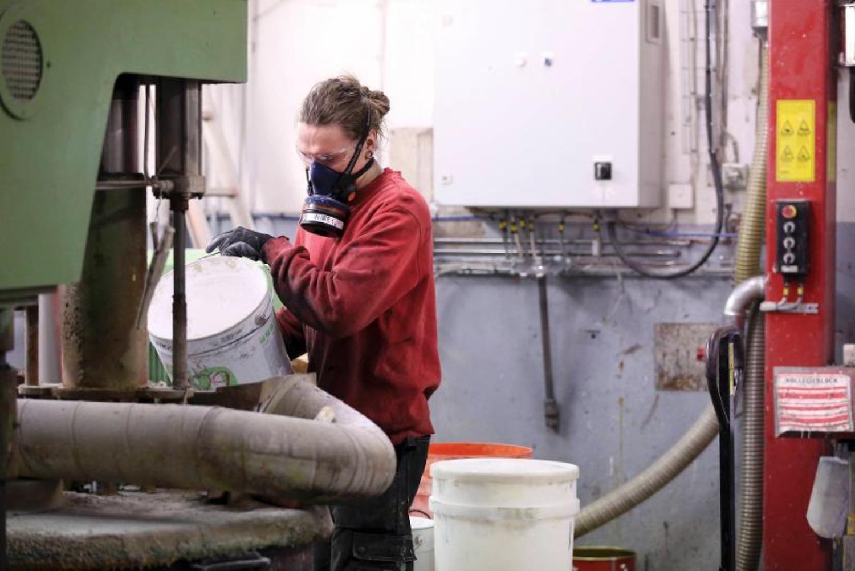 En person i skyddsmask blandar färg