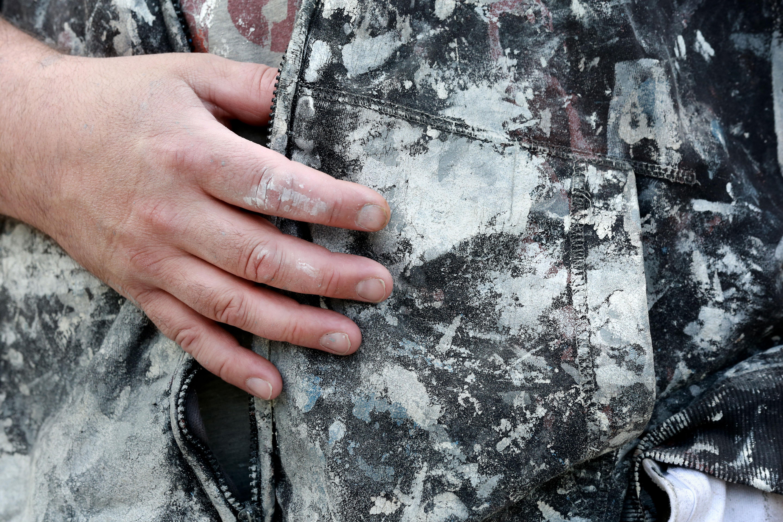 En person med handen i fickan på byxor med färgfläckar