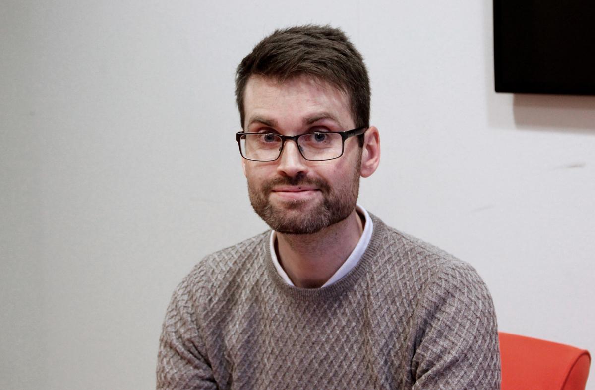 Bilden föreställer en man iklädd en grå tröja som sitter på en orange stol mot en vit bakgrund. Mannen har kort, mörkt hår, skägg och glasögon.