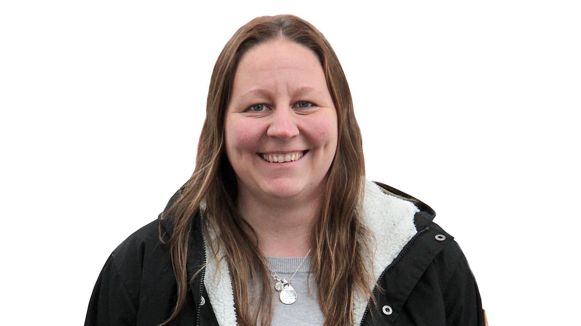 Bilden föreställer en leende kvinna med långt, brunt hår. Hon har på sig en mörk, uppknäppt jacka och en grå tröja. Runt halsen har hon en tunn kedja med ett droppformat metallhänge på.
