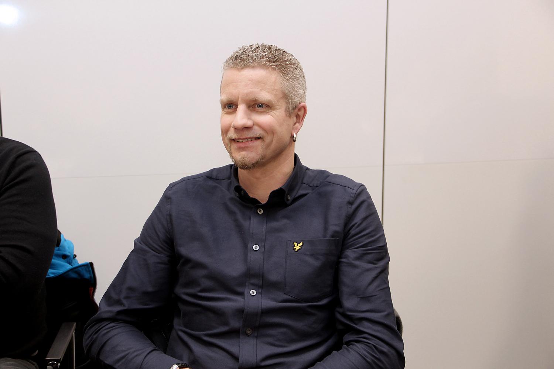 BIlden föreställer Samuel Jarenil Han har kort hår och skägg, och en ring i ena örat. Han är klädd i mörkblå skjorta och sitter ned på ett möte.