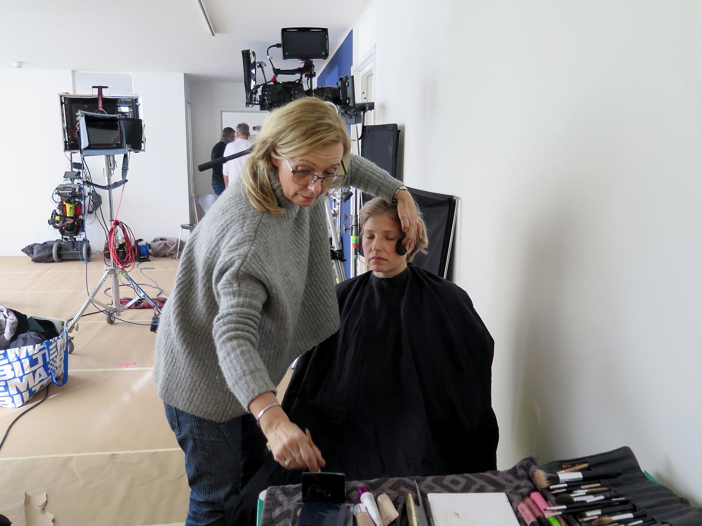 Bilden föreställer en filmstudio, där en person i grå kofta håller på att sminka en annan person med ett svart skyddsplagg på sig.