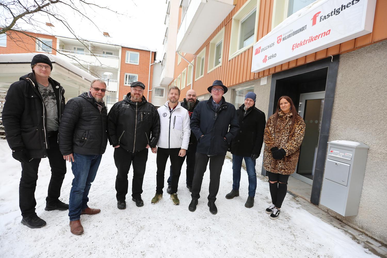 Bilden är en gruppbild utomhus, som föreställer åtta personer som står i snön framför en byggnad vars skylt har 6F-förbundens logotyper på sig. Det är Byggnads, Målarna, Fastighets, Seko och Elektrikernas logotyper.