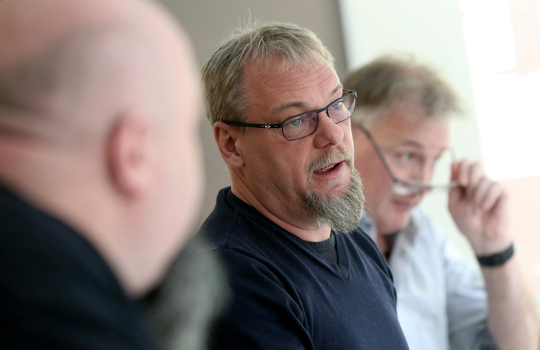 Bilden föreställer Jan-Olov Gustafsson. Han har kort hår, skägg och glasögon. Han sitter mellan två andra personer vid ett mötesbord.