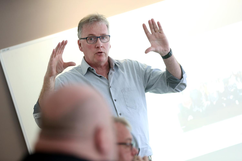 Bilden föreställer MÅlareförbundets ordförande Mikael Johansson, som står och gestikulerar med händerna framför en whiteboard. Han har blå skjorta och glasögon på sig.