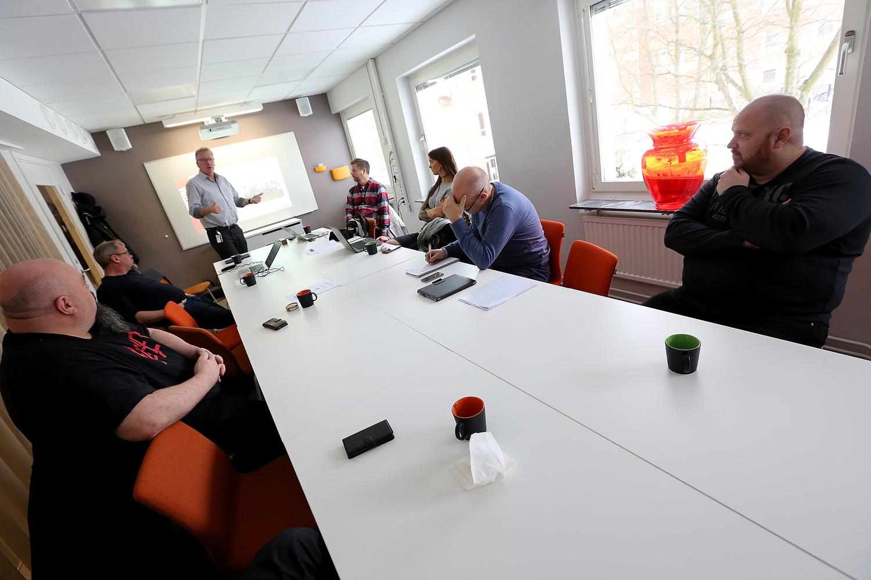 Bilden föreställer ett långt mötesbord där sex personer sitter. De tittar mot ena kortsidan, där Målareförbundets ordförande Mikael Johansson står och pratar framför en whiteboard-tavla.