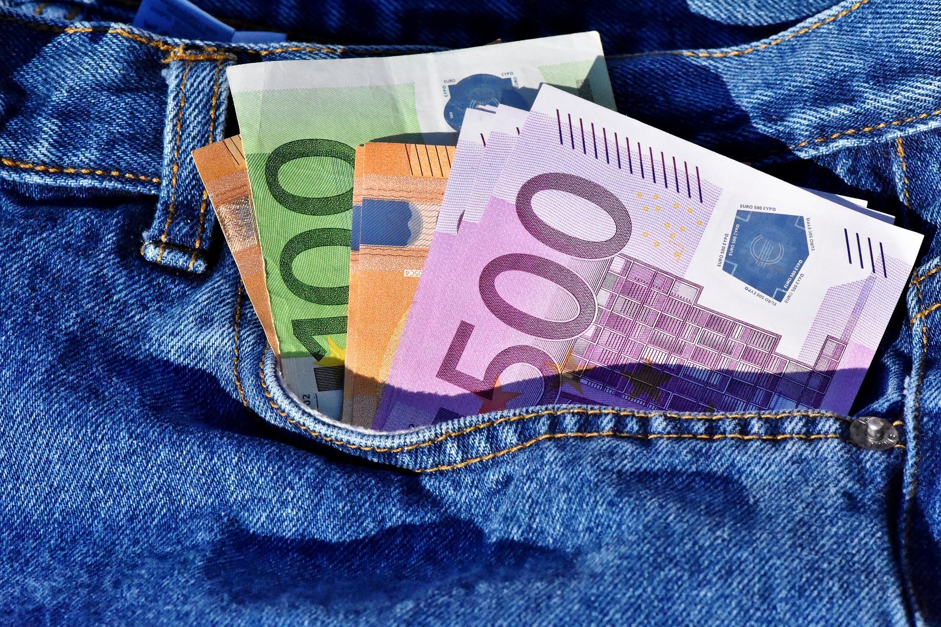 Bilden är en närbild på sidofickan på ett par blå jeans. Sju olika Euro-sedlar sticker upp ur fickan.