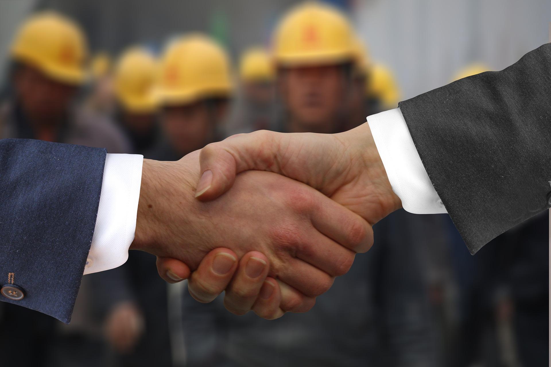 Bilden föreställer ett handslag mellan två händer vars armar ä klädda i kostym. I bakgrunden ser man en samling suddiga gestalter med gula bygghjälmar på.
