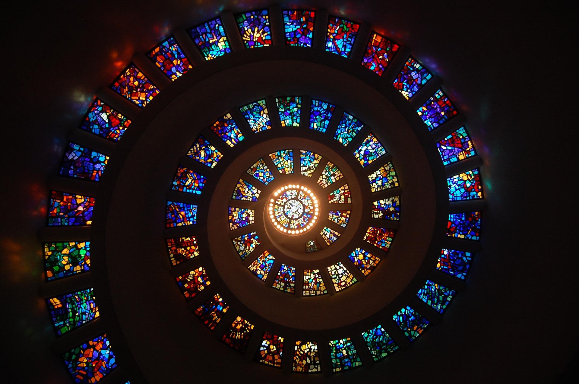 Bilden föreställer en spiral bestående av dussintals förgglada moasaikfönster som ringlar upp längs ett kupolformat tak. I mitten är ett runt fönster som släpper in starkt ljus.