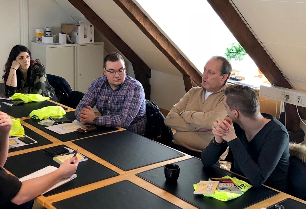 Bilden föreställer fem personer runt ett bord med skrivunderlägg och informationsmaterial på.