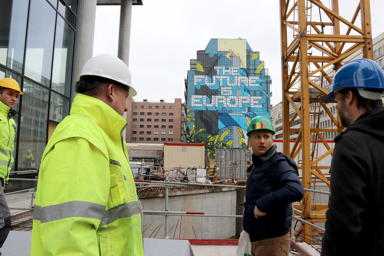 Bilden föreställer fyra byggnadsarbetare på en byggarbetsplats i Bryssel. I bakgrunden ser man en byggnad med texten The Future Is Europe på.