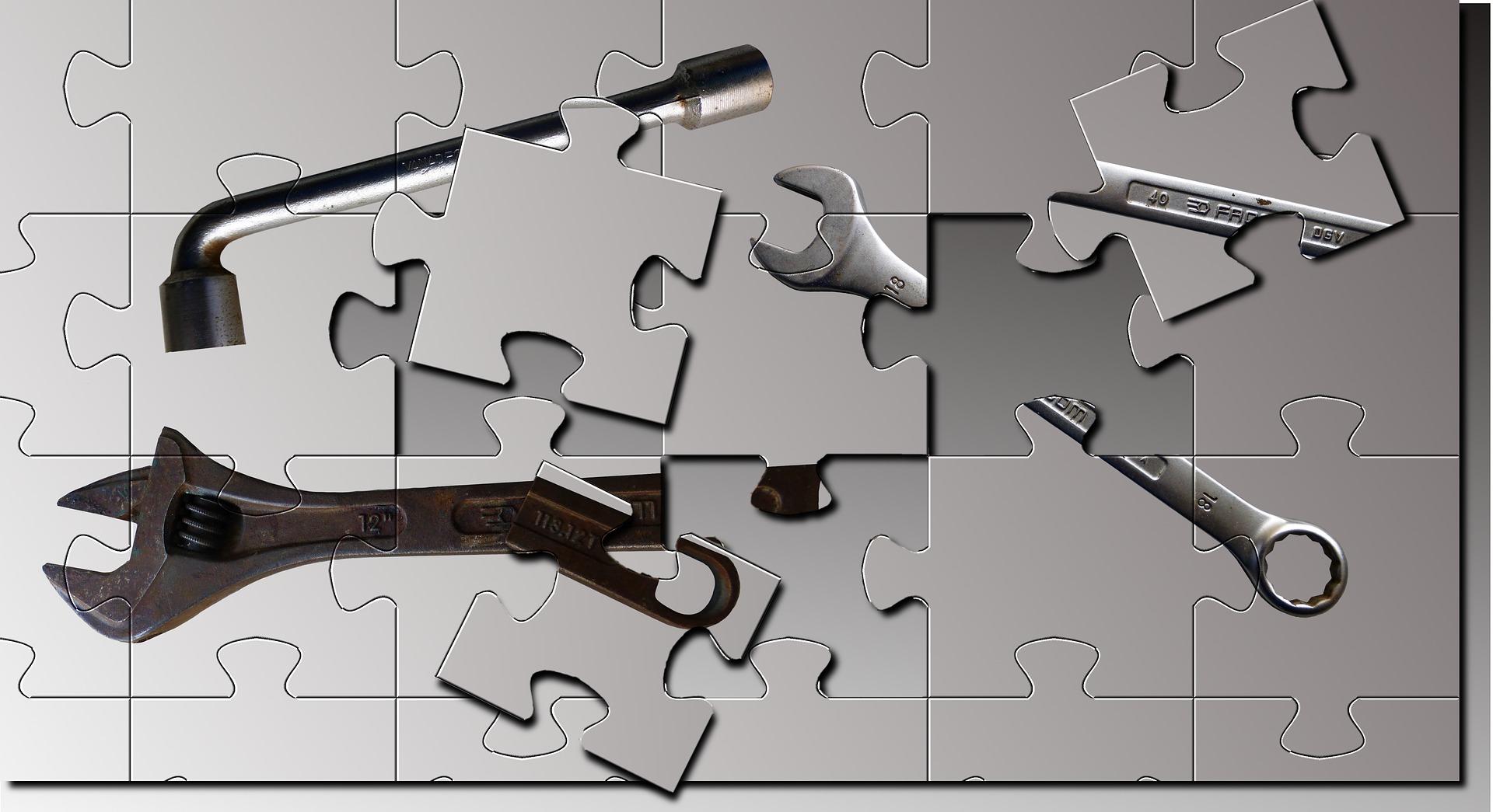 Bilden föreställer ett pussel med grå bakgrund, innehållande ett fälgkors, en skiftnyckel och en blocknyckel. Tre av bitarna i pusslet ligger fel, vilket resulterar i hål i bilden.
