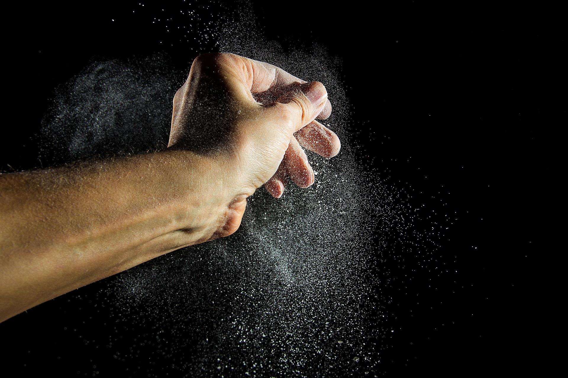 Bilden föreställer en hand som släpper ett moln av vitt damm mot en svart bakgrund.