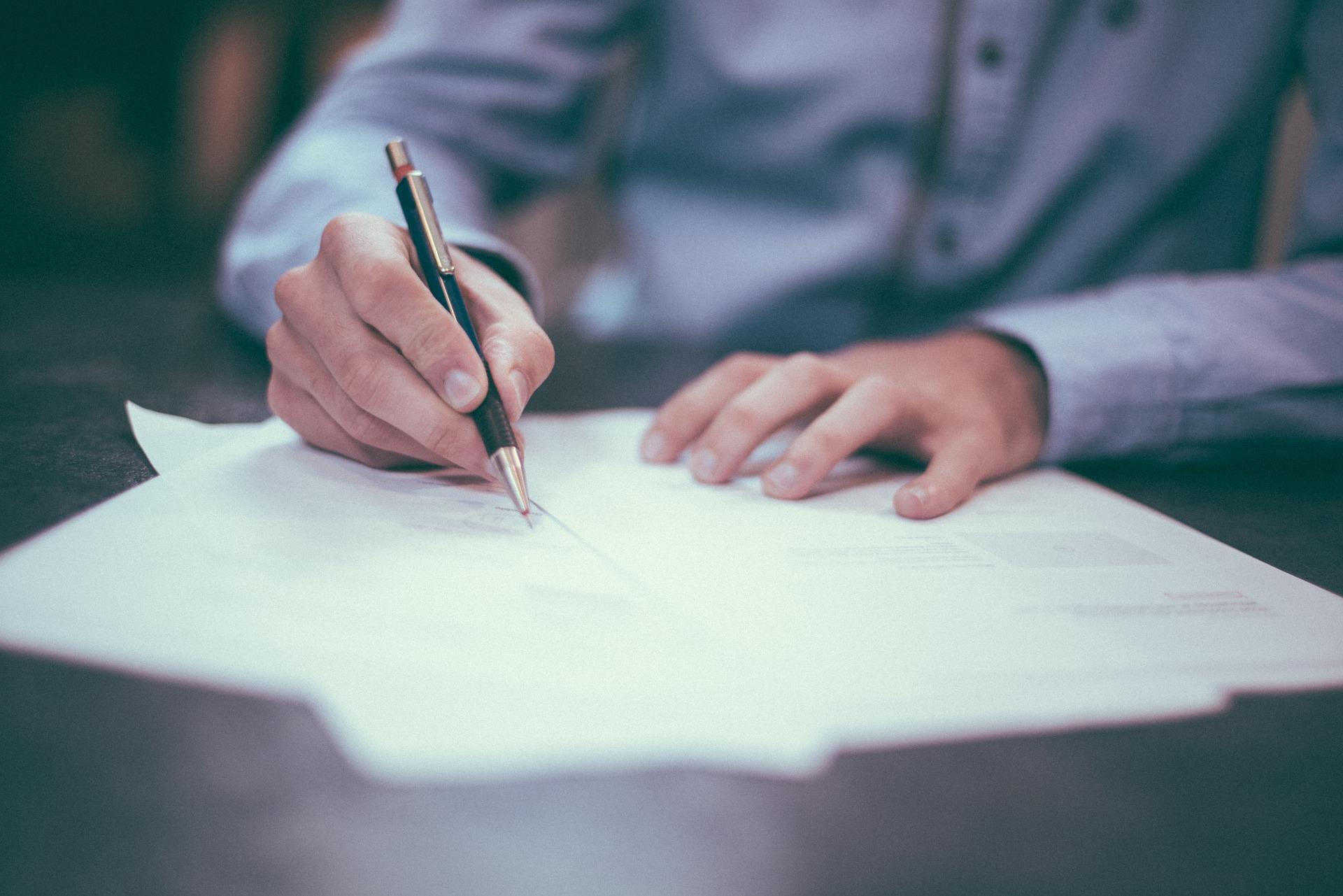 En person skriver på ett papper