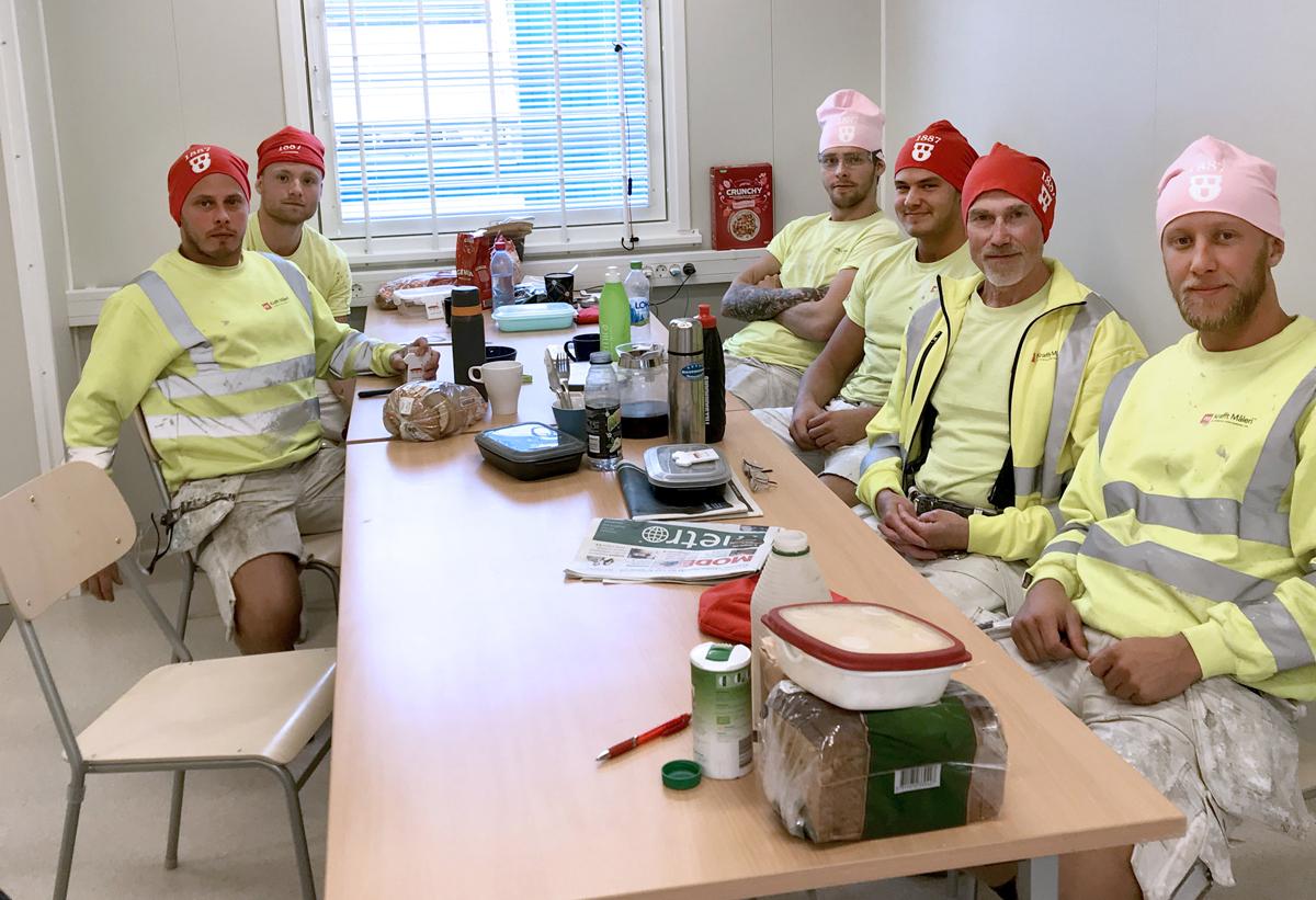 Sex personer sitter vid ett bord i ett lunchrum. De har alla mössor med Målareförbundets logga på.