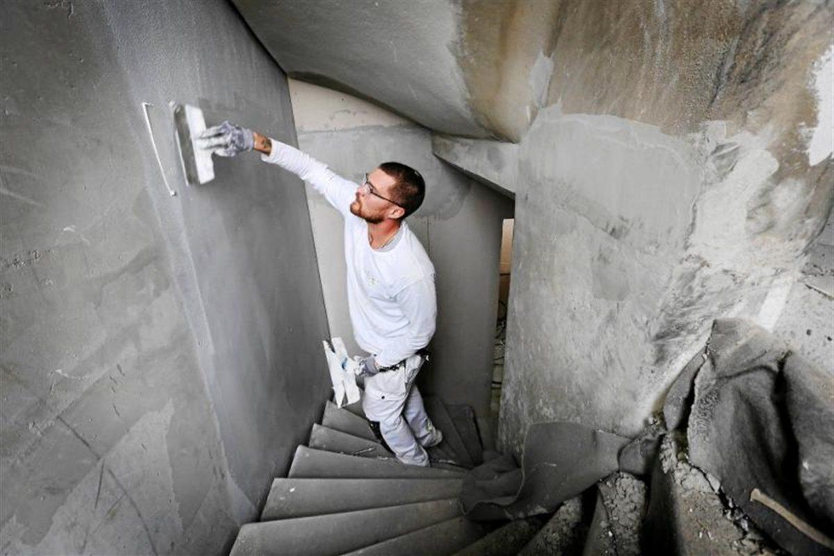 En person spacklar väggen i en trappa.