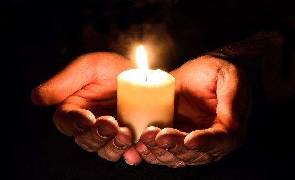 Två kupade händer som håller i ett levande ljus i mörkret.