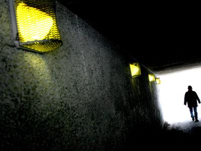 Silhuetten av en person i slutet av en gångtunnel