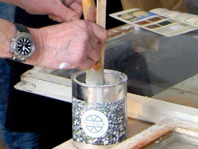 En person doppar en pensel i en burk linoljefärg