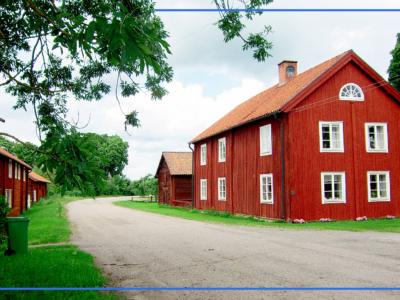 Ett rött hus på en somrig lantväg