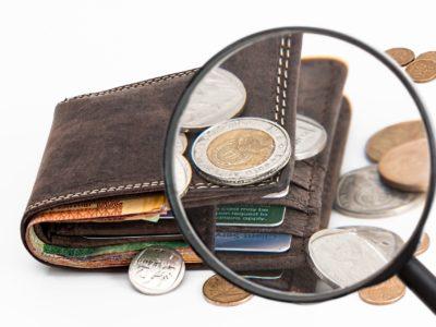 Ett förstoringsglas som zoomar in på en plånbok med pengar i
