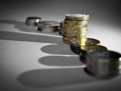 En rad med mynt-travar med långa skuggor