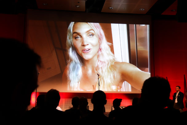 Linnéa Claeson på en stor skärm. I förgrunden silhuetterna av flera åskådare under Målarnas kongressmiddag.