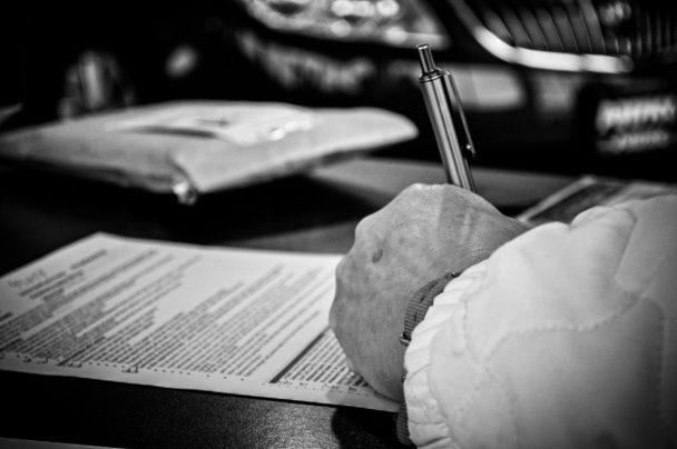 En hand som skriver under på ett papper.