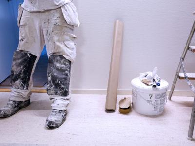 Benen och fötterna på en målare som står vid en vägg med sina verktyg