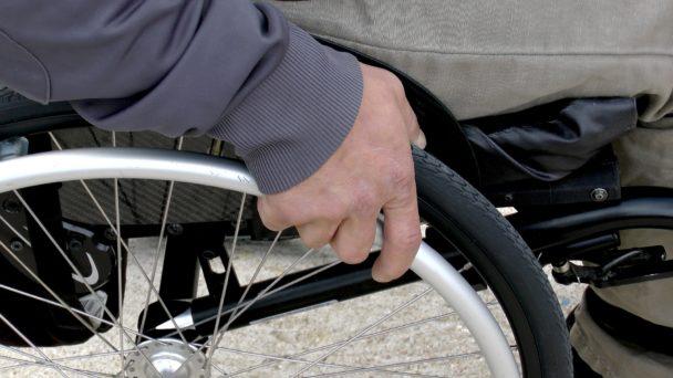 En närbild på en hand som håller i däcket på en rullstol.