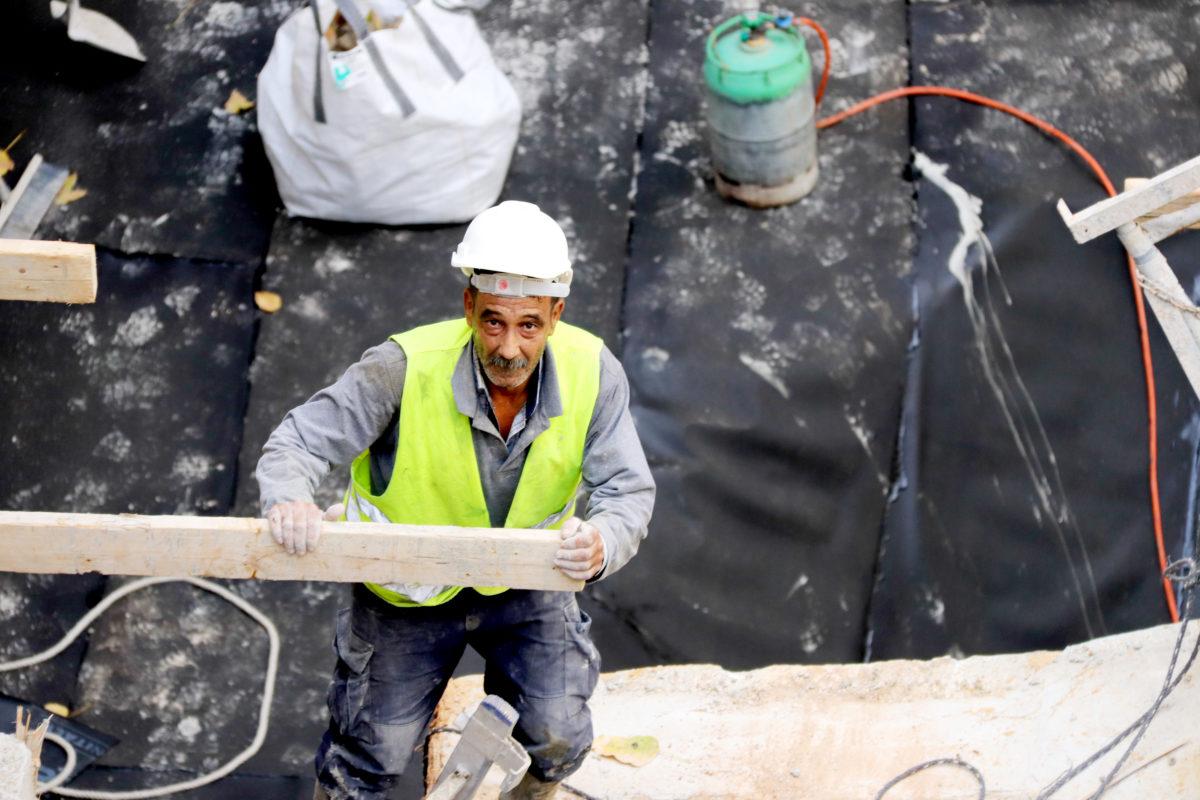 En man i bygghjälm och reflexväst på en byggarbetsplats