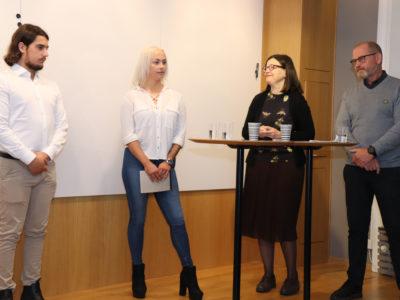 Fyra personer står längst fram i en föreläsningssal.