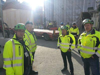 Fyra personer i reflexjackor står på ett bygge.