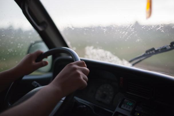 Två händer på ratten till en bil.