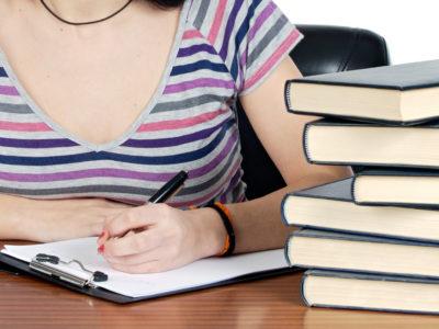 En ung person sitter och skriver invid en trave böcker på ett bord.