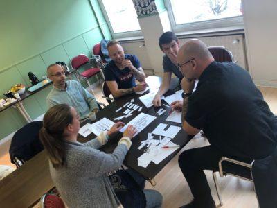 Några personer sitter runt ett bord i ett mötesrum