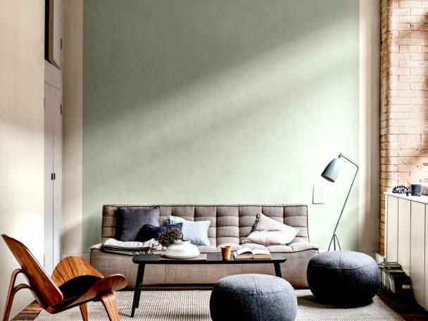 Ett vardagsrum med den gröna färgen Tranquil Dawn på väggen. Solljus lyser in genom fönstret.