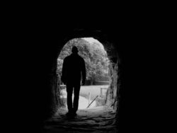 En person går i en mörk tunnel och avtecknar sig i silhuett mot snölandskapet utanför.