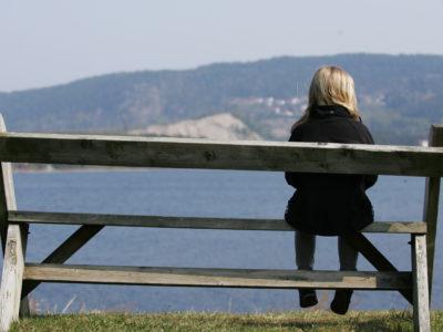 En person sitter ensam längst ut på en bänk som är vänd mot en sjö.