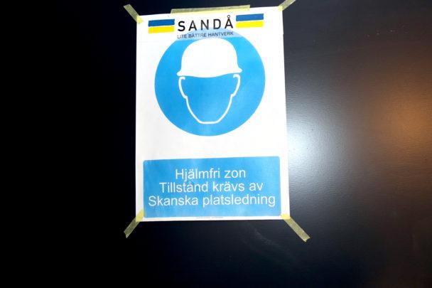 """En utskriven skylt med en stiliserad bild på en person i bygghjälm, där det även står: SANDÅ. """"Hjälmfri zon. Tillstånd krävs av Skanska platsledning""""."""