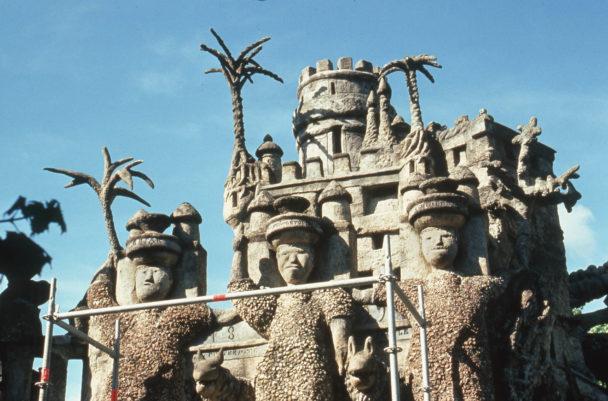 Ett sandfärgat palats med krenelerade torn. Framför byggnaden står tre människoskulpturer i samma färg.