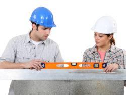 En man och en kvinna i bygghjälmar samarbetar för att jämna ut ett vattenpass.