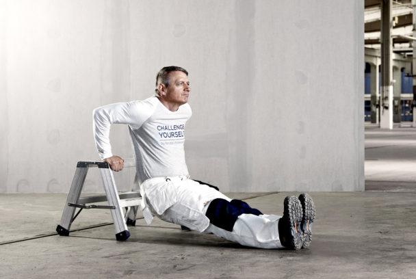 En man sitter på golvet framför en stegpall, och lyfter upp sin kropp med hjälp av händerna mot pallens överdel.