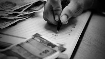 Svartvit bild på en hand som skriver i en anteckningsbok, omgiven av sedlar.