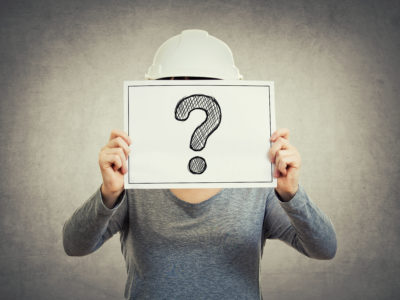 En person i bygghjälm håller upp en skylt med ett frågetecken på.