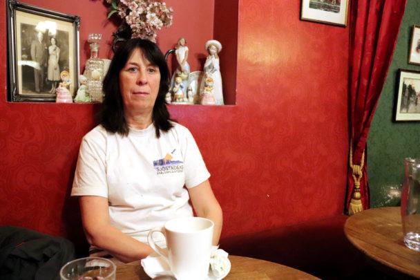 Mia Wemmenlöv i en soffa med en kopp på bordet framför sig.